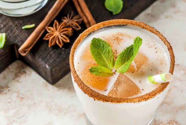 Traditionelles indisches getränk ist eistee oder chai masala mit eiswürfeln aus chai, milch und minze. mit gestreiften strohhalmen auf einem holzbrett. auf hellbeigem steintisch. kopieren sie platz
