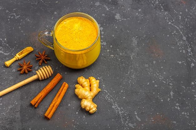 Traditionelles indisches getränk kurkuma milch ist goldene milch in glasbecher mit zimt, anis stern, kurkuma auf dunklem hintergrund. gewichtsverlust, gesundes und biologisches getränk