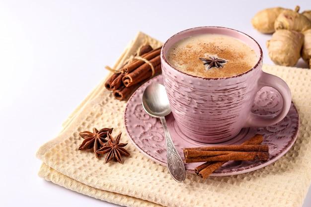 Traditionelles indisches getränk - masala-tee mit gewürzen in der rosa tasse auf einer weißen oberfläche, horizontale ausrichtung, kopienraum
