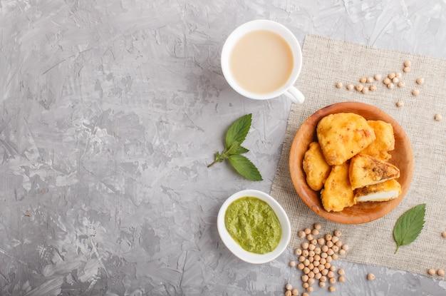 Traditionelles indisches lebensmittel paneer pakora in der hölzernen platte mit tadellosem chutney auf einem grauen konkreten copyspace. ansicht von oben.