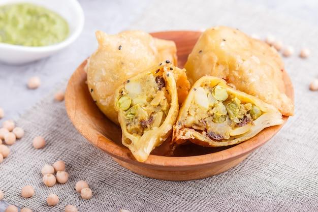 Traditionelles indisches lebensmittel samosa in der hölzernen platte mit tadellosem chutney