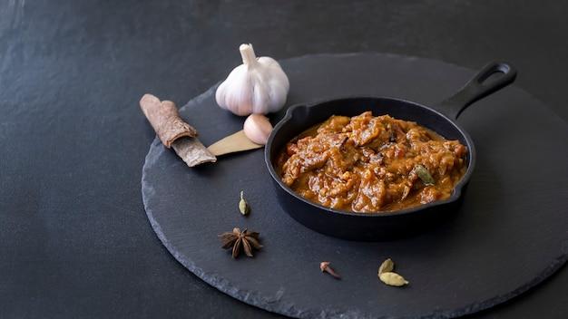 Traditionelles indisches rindfleisch-curry serviert aus eisenguss weltküche schwarzer schieferhintergrund