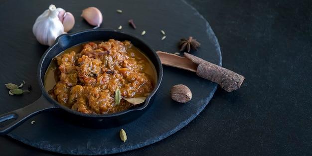 Traditionelles indisches rindfleisch-curry serviert eisenguss weltküche schwarzer schieferhintergrund bannergröße