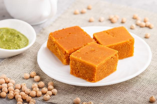 Traditionelles indisches süßigkeit burfi in der weißen platte mit tadellosem chutney