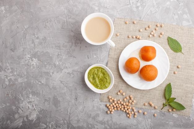 Traditionelles indisches süßigkeit gulab jamun in der weißen platte mit tadellosem chutney auf einem grauen konkreten copyspace. ansicht von oben.