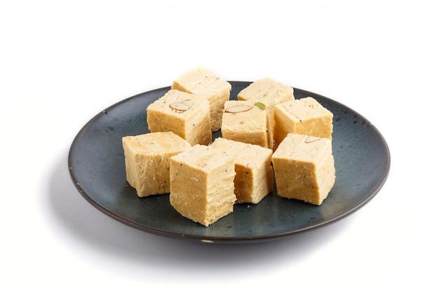 Traditionelles indisches süßigkeit soan papdi in der blauen keramischen platte lokalisiert auf einem weißen hintergrund