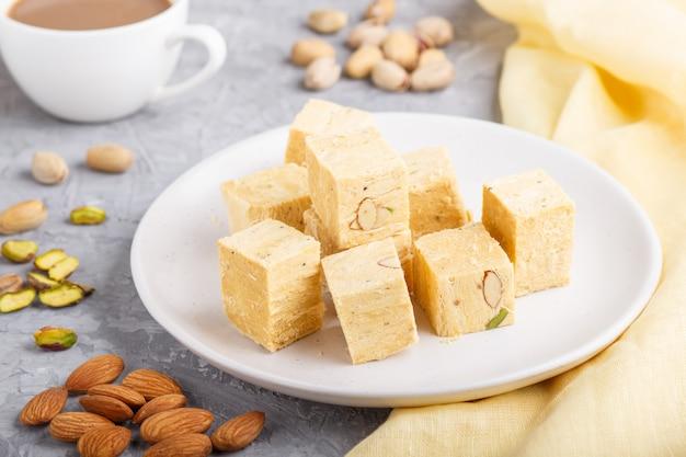 Traditionelles indisches süßigkeit soan papdi in der weißen platte mit mandel und pistache auf einem grauen beton.