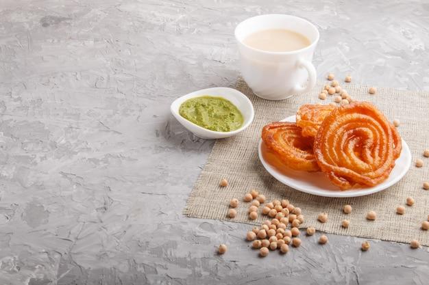 Traditionelles indisches süßigkeitsjalebi in der weißen platte mit tadellosem chutney auf einem grauen konkreten copyspace. seitenansicht.