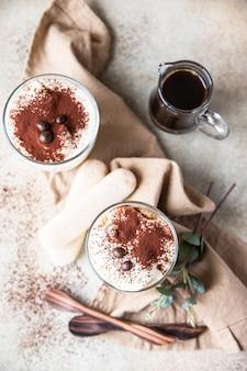 Traditionelles italienisches dessert tiramisu im glas portionsdessert mit kaffeegeschmack und kakao