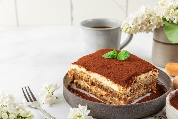 Traditionelles italienisches dessert tiramisu in einem teller mit kaffeetasse, dessertgabel und blumen auf weißer oberfläche für leckeres frühstück