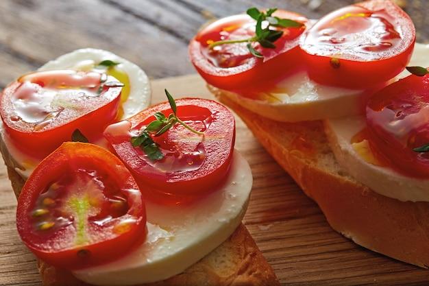 Traditionelles italienisches essen mit bruschetta - kirschtomaten, frischkäse, basilikumblätter auf einem holzbrett. nahaufnahme. gesunder natürlicher snack.