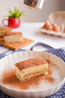 Traditionelles italienisches gourmet-tiramisu-dessert mit schokoladenpulver