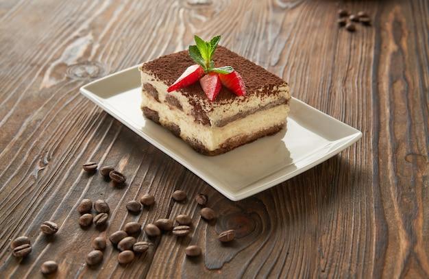 Traditionelles italienisches tiramisu-dessert auf holzhintergrund der weißen platte mit kaffeebohnen