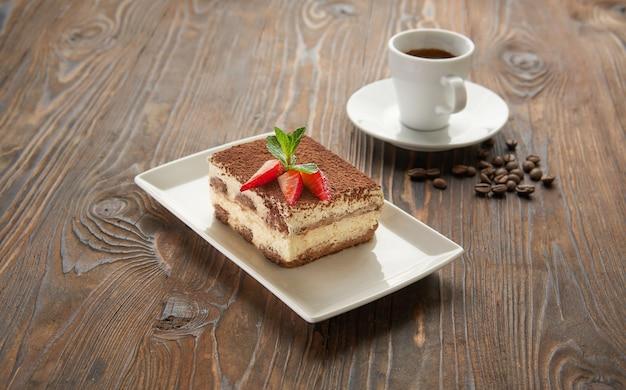 Traditionelles italienisches tiramisu-dessert auf weißem teller mit tasse espresso-kaffee auf holztisch