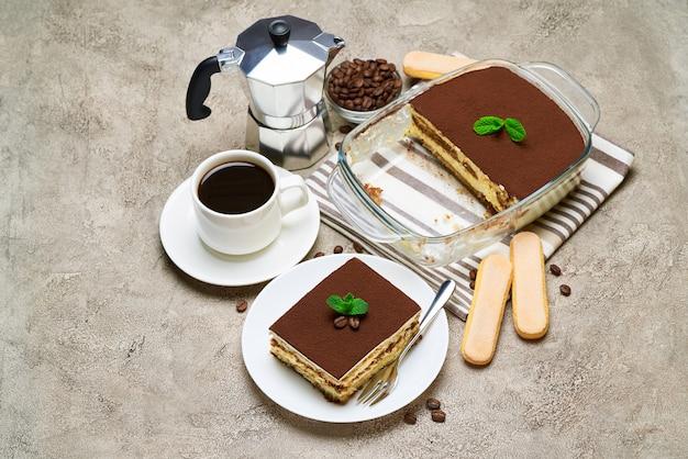 Traditionelles italienisches tiramisu-dessert in glasbackform und portion auf grauem betontisch