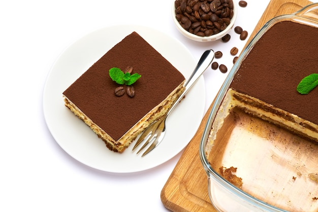 Traditionelles italienisches tiramisu-dessert in glasbackform und portion auf teller auf weiß