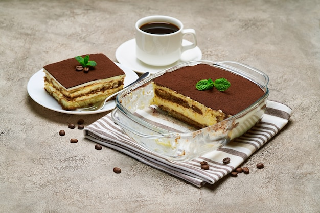 Traditionelles italienisches tiramisu-dessert in glasbackform und portion