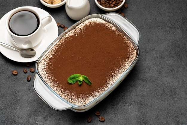 Traditionelles italienisches tiramisu-dessert in glasbackform und tasse frischen heißen espressokaffee auf betonhintergrund oder -tisch