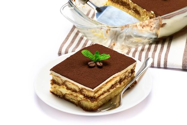 Traditionelles italienisches tiramisu-dessert in glasbackformportion auf teller und schulterblatt lokalisiert auf weiß Premium Fotos