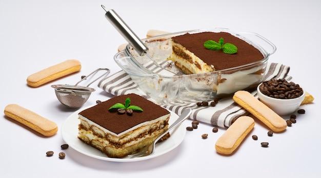 Traditionelles italienisches tiramisu-dessert in glasbackformportion auf teller und schulterblatt lokalisiert auf weiß