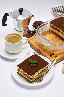 Traditionelles italienisches tiramisu-dessert in glasbackformportion auf teller und schulterblattisolatet auf weiß