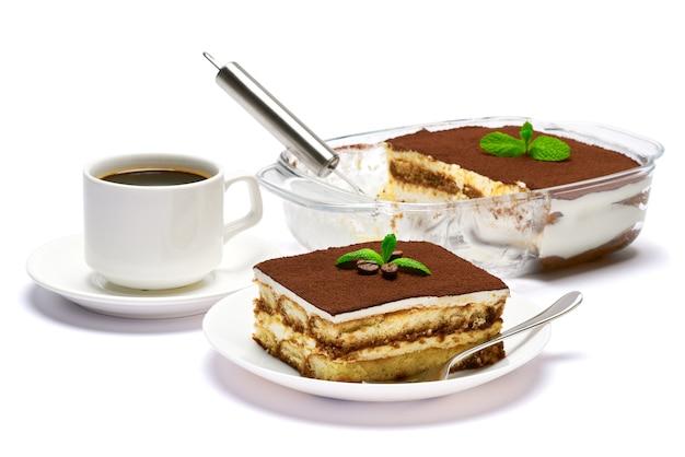 Traditionelles italienisches tiramisu-dessert in glasbackformportion auf teller und tasse kaffee-isolatet auf weiß