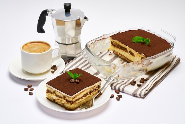 Traditionelles italienisches tiramisu-dessert in glasbackformportion auf teller und tasse kaffee lokalisiert auf weiß