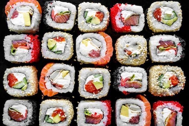 Traditionelles japanisches essen - sush rollt auf schwarzem hintergrund. draufsicht