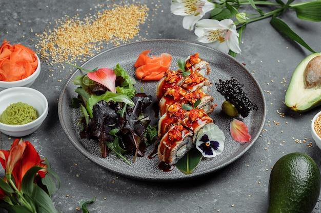 Traditionelles japanisches essen. sushi rollt mit aal auf einem grau. platz für eine inschrift.