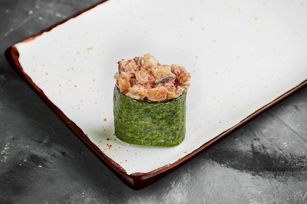 Traditionelles japanisches gunkan-sushi mit aal, kaviar und würziger sauce in nori auf einem weißen teller. nahaufnahme, selektiver fokus