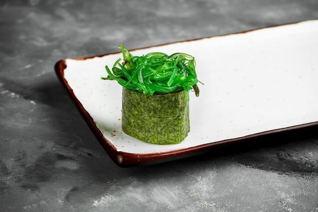 Traditionelles japanisches gunkan-sushi mit hiyashi, kaviar und würziger sauce in nori auf einem weißen teller. nahaufnahme, selektiver fokus