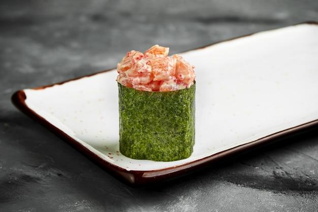 Traditionelles japanisches gunkan-sushi mit lachs, kaviar und würziger sauce in nori auf einem weißen teller. nahaufnahme, selektiver fokus