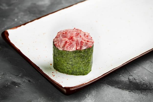 Traditionelles japanisches gunkan-sushi mit thunfisch, kaviar und würziger sauce in nori auf einem weißen teller. nahaufnahme, selektiver fokus