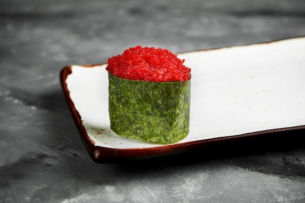 Traditionelles japanisches gunkan-sushi mit tobiko-kaviar und würziger sauce in nori auf einem weißen teller. nahaufnahme, selektiver fokus