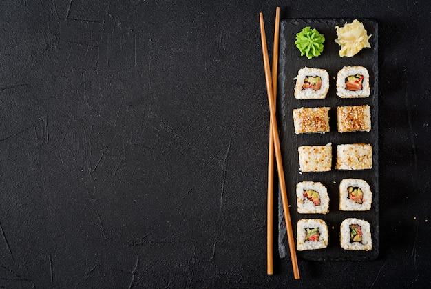 Traditionelles japanisches lebensmittel - sushi, brötchen und essstäbchen für sushi auf einem dunklen hintergrund. draufsicht