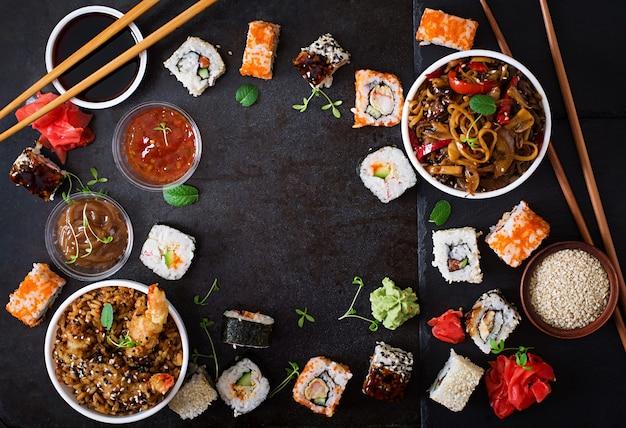 Traditionelles japanisches lebensmittel - sushi, rollen, reis mit garnele und udonnudeln mit huhn und pilzen auf einem dunklen hintergrund. ansicht von oben