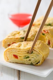 Traditionelles japanisches omelett tamagoyaki auf weißem holztisch.