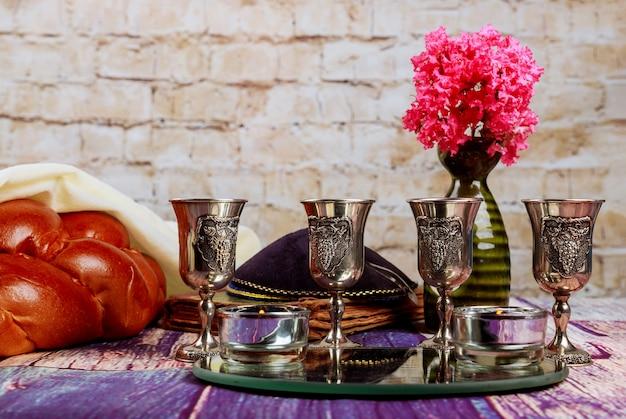 Traditionelles jüdisches sabbat-shalom-ritual frisches challa-brot auf kiddusch vier tasse koscheren rotwein