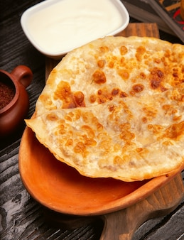 Traditionelles kaukasisches gutab, kutab, gozleme mit sumakh und joghurt in der hölzernen platte.
