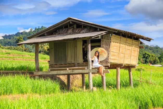 Traditionelles kostüm der asiatinabnutzung, das im terrassenreisbauernhof sitzt
