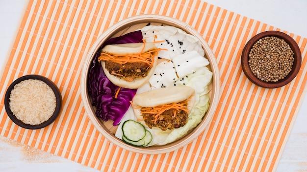 Traditionelles lebensmittel gua bao im dampfer mit salat auf tischset