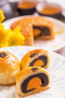 Traditionelles lebensmittelkonzept des mid-autumn festivals - schöner geschnittener mondkuchen auf blauem musterteller auf weißem hintergrund mit blume, nahaufnahme, kopienraum