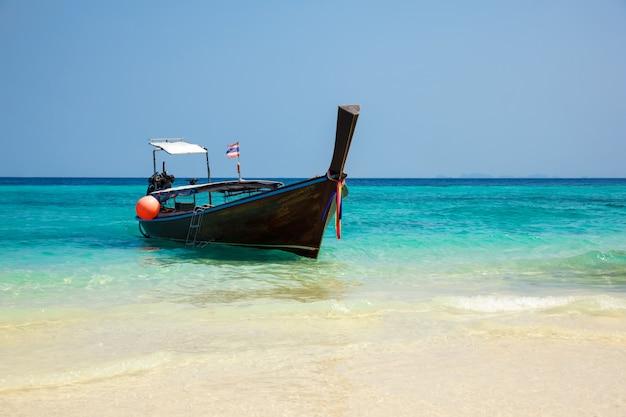 Traditionelles longtail-boot auf dem tropischen strand nahe koh phi phi island, thailand