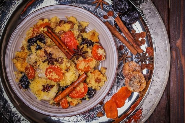 Traditionelles marokkanisches huhn mit getrockneten früchten und gewürzen.
