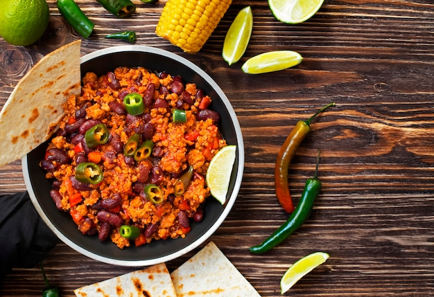 Traditionelles mexikanisches chili con carne diente auf einem rustikalen holztisch in einer wanne mit mais, mexikanischem tortillabrot, kalk und jalapeño. ansicht von oben.