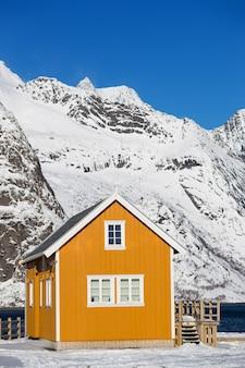 Traditionelles norwegisches holzhaus rorbu am ufer des fjords und der berge in der ferne. lofoten-inseln. norwegen. weltreise