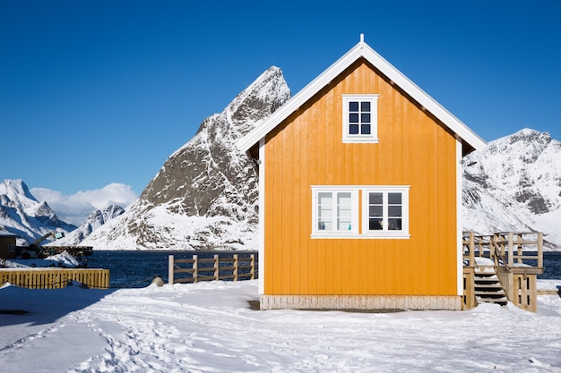 Traditionelles norwegisches holzhaus rorbu am ufer des fjords und der berge in der ferne. lofoten-inseln. norwegen.