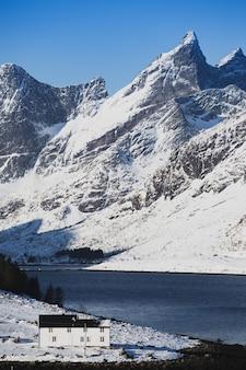 Traditionelles norwegisches holzhaus steht am ufer des fjords und der berge in der ferne. lofoten-inseln. norwegen. weltreise
