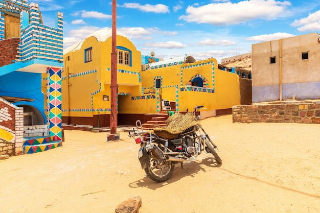 Traditionelles nubisches dorf in afrika und ein authentisches motorrad, ägypten.