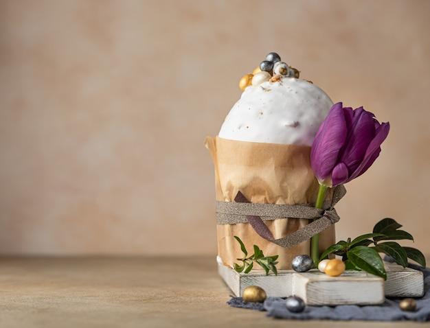 Traditionelles orthodoxes süßes brot kulich verziert mit eiern und tulpen in form von baiser-zuckergussbonbons